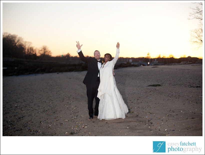 bride and groom waving goodbye from the beach