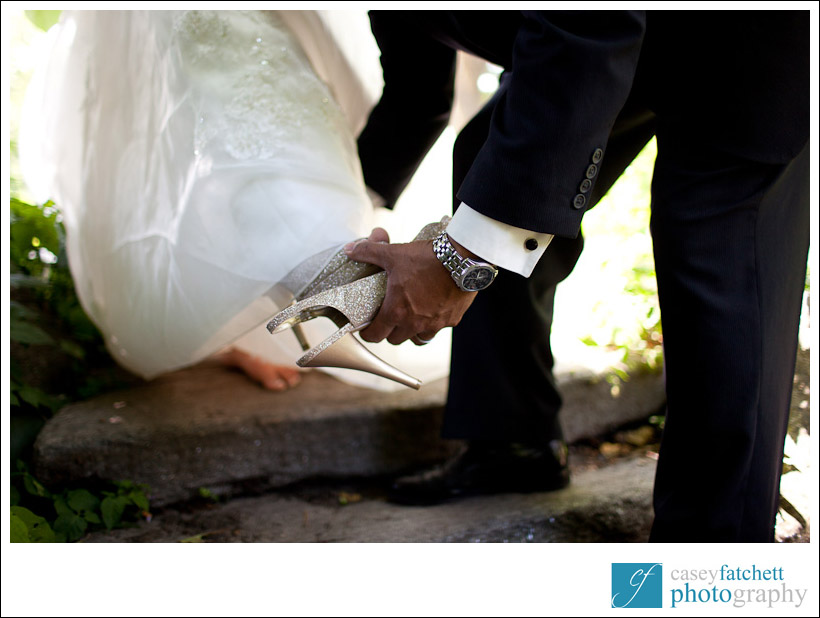 groom taking off bride's shoes