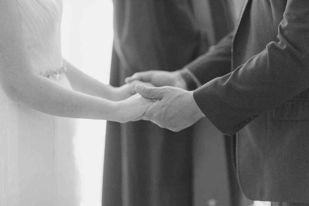 couple holding hands during wedding ceremony