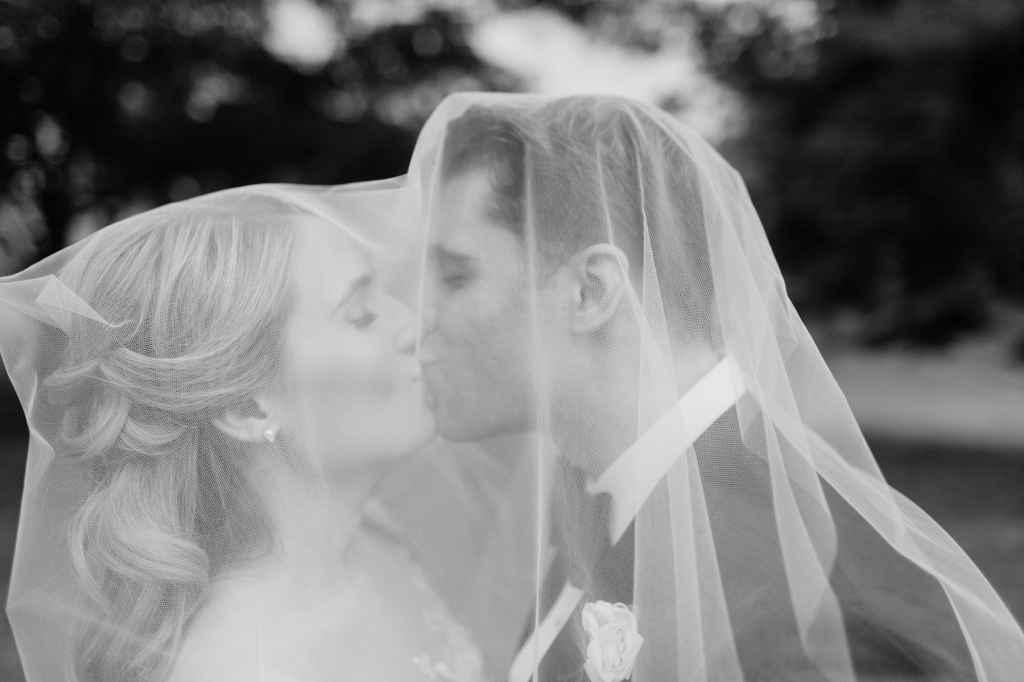 elegant wedding photos bride and groom kissing under the veil